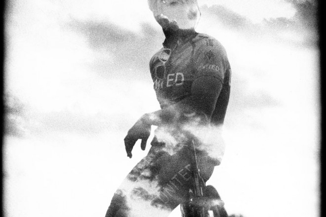 Double-exposure, in black and white, of a cyclist and clouds.